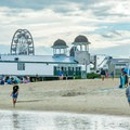 Beachgoers enjoy the shoreline.- Old Orchard Beach