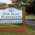 A large sign along the road identifies the plantation.- Oak Alley Plantation