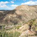 A hiker pausing to take in the view.- Climbers Loop Trail
