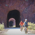 The first of five tunnels along the trail. Cycling the level grade is a popular activity.- Historic Railroad Trail