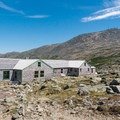 Lakes of the Clouds Hut with Mount Washington behind it.- Lakes of the Clouds Hut + Mount Washington