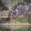 Oeschinensee Lake is surrounded by numerous tall waterfalls.- Oeschinensee + Heuberg Loop