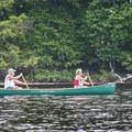 Canoes paddling across the lake.- Rollins Pond Loop