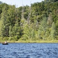 A canoe paddler across the water.- Deer River Flow