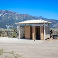 Shaded outhouses and a horse wash trough are located in the parking area.- North Loop Hiking Trail