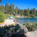 The sandy shore and calm water provide a family-friendly beach area.- Cave Rock State Park