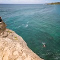 Cliff jumpers leap from this 25-foot rock face over shallow water.- Shipwreck's Beach