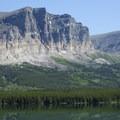 Apikuni Mountain towering over the head of Lake Sherburne.- Cracker Lake