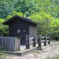 A vault toilet and a trash can are the only amenities in this camp.- Alder Trail Camp