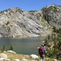Granite mountainsides slide down into glittering alpine lakes. - The Beaten Path