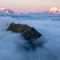 Bettmeralp pokes out of the clouds in the foregroud with the Matterhorn, the Dufourspitze, and Dent Blanche in the distance.- Fiescheralp to Eggishorn Hike