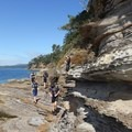 The shore begins to narrow into a shelf that is easy enough to walk. - Coasteering on Sangster Island