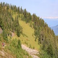 Hikers make their way alongside the ridge of Lilly Basin Trail with Mount Rainier shrouded in smoke.- Goat Rocks Thru-hike
