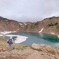 A hiker takes in the view of Goat Lake.- Goat Rocks Thru-hike