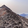 Hikers make their way up the climber's trail to the summit of Old Snowy Mountain with Mount Adams on the right.- Goat Rocks Thru-hike