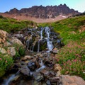 Headwaters of the Cispus River pour through a lush, cascading, wildflower-filled meadow with a rampart cliff above.- Goat Rocks Thru-hike
