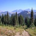 The Nannie Ridge Trail climbs southwest above the Sheep Lake saddle, affording final views of the southern Goat Rocks peaks.- Goat Rocks Thru-hike