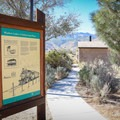 A couple of interpretive signs and a vault toilet sit in the parking lot.- Wetlands Loop
