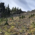 Hikers make their way through an open hillside.- Mount Adams Circumambulation