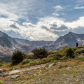 A hiker takes a moment to admire the view with Mount Neva on the right and Mount Jasper on the left.- Neva Backcountry Zone