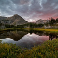 A beautiful sunset reflected in a small lake by the creek, with Mount Neva far in the background.- Neva Backcountry Zone