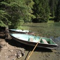 Boats along the shore of Fifth Lake.- Valley of the Five Lakes