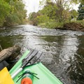 Fast moving low rapids through town.- Shiawassee River Trail: Fenton to Linden