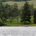 A kayaker paddles along the shoreline.- Shawnee State Park