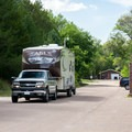 A trailer enters the camping area through a memorial gateway.- Bessey Recreation Complex + Campground