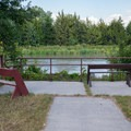 A seating area is alongside the river.- Bessey Recreation Complex + Campground