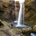 The falls drop about 30 meters, with a path allowing hikers to walk behind the fall.- Kvernufoss (Sigurfoss) Waterfall