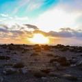 The black sand and stone beneath a setting sun at Reynisfjara.- Reynisfjara Beach