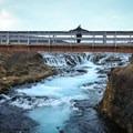 A pedestrian bridge offers tranquil views over the scenic waterfalls.- Brúarfoss