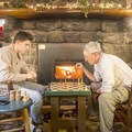 Playing chess in front of the fireplace.- Adirondack Loj
