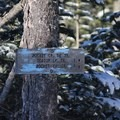 A sign posted to a tree on the north end of the parking area.- Bennett Pass Sno Park