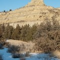 Buttes and hills rise above the forested drainages. Caprock Coulee Trail.- Caprock Coulee Trail