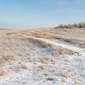Hiking along a winding path through open fields.- Bennett-Cottonwood Loop via Maah Daah Hey Trail