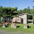 An information sign and vault toilet at the Baker Beach trailhead.- Baker Beach