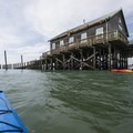 View of Pier's End Boathouse (historic Coast Guard boathouse) from a kayak.- The Tillamook Bay Heritage Route