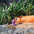 A woman beats rice on the path leading up toward Lokpa.- Nepal Undiscovered, Part 1: Tsum Valley Trek