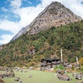 The village of Gho under a rocky pyramid-shaped mountain.- Nepal Undiscovered, Part 1: Tsum Valley Trek