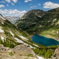 Along the Pacific Northwest Trail, looking down on Stoney Indian Lake from the top of Stoney Indian Pass.- 10 Incredible Backpacking Trips You Should Do Next Summer