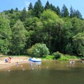 Campers enjoy the sandy swimming beach on a warm summer's day.- Loon Lake Lodge + RV Resort