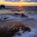 Sun dips below the horizon with agates on the south end of the cove.- Roads End State Recreation Site