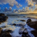 Sunlight breaks through the clouds as waves crash on the rocks.- D.T. Fleming Beach Park