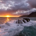 Waves pour over a rock creating a waterfall down the other side with a beautiful sunset on Makua Beach.- Makua Beach