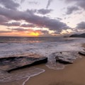 Sun breaks through the clouds as waves gently beat rocks in the surf.- Ma'ili Beach Park