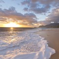 The warm sun sets as the inviting surf gently moves across the sand.- Ma'ili Beach Park
