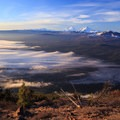 Morning light over low-lying fog as the Three Sisters look on from the horizon.- Black Butte Hike