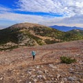 A hiker ascends the false summit with Bald Peak in the background.- Wheeler Peak